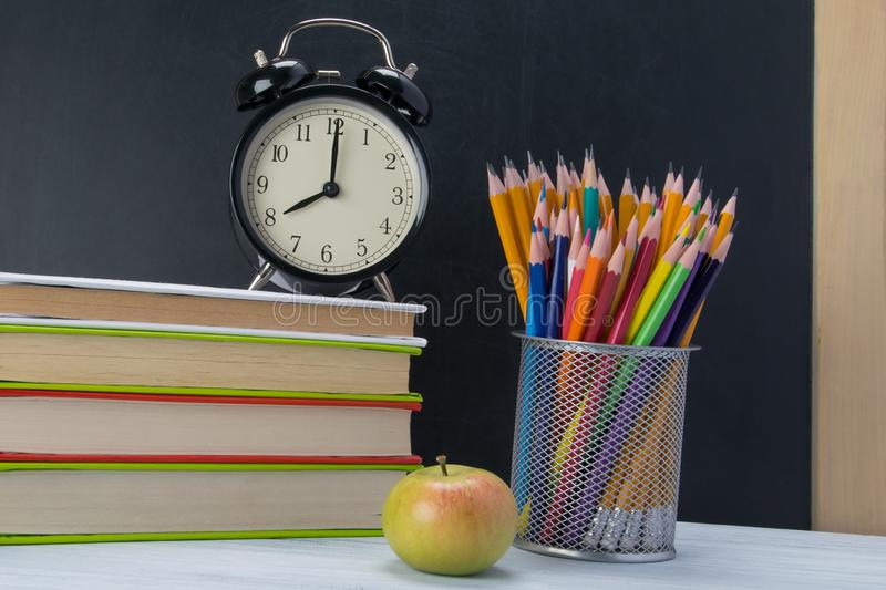 On the table a stack of books with an alarm clock on top, a snack break royalty free stock photos