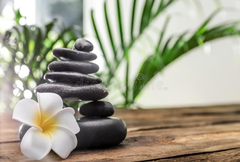 Table with stack of stones, flower and green leaves on background, space for text. Zen concept. Table with stack of stones, flower and blurred green leaves on stock photography