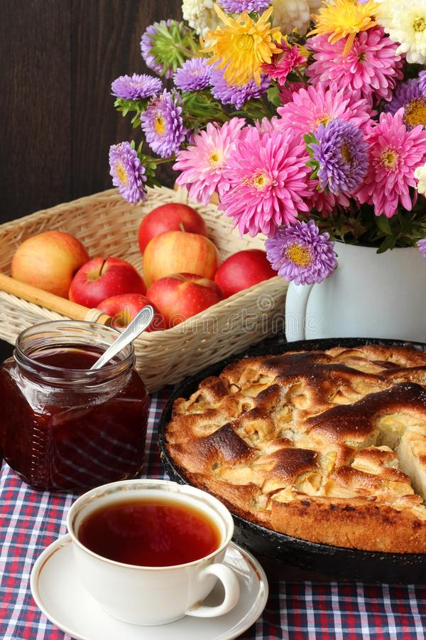 Table-still life with pie, apples, jam and tea. stock images