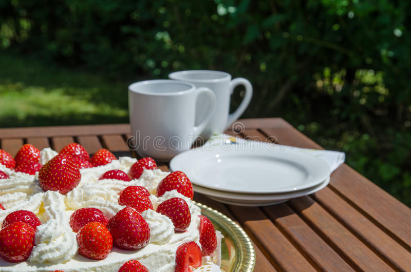 Table with strawberry cake and coffee cups in background stock photography
