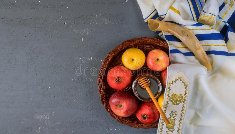 On the table in the synagogue are the symbols of Rosh Hashanah apple and pomegranate, shofar talith. Table in the synagogue are symbols of Rosh Hashanah apple royalty free stock images