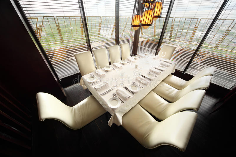 Table and ten white chairs in empty restaurant. Table with white tablecloth and serving and ten white chairs in empty lit restaurant stock photos