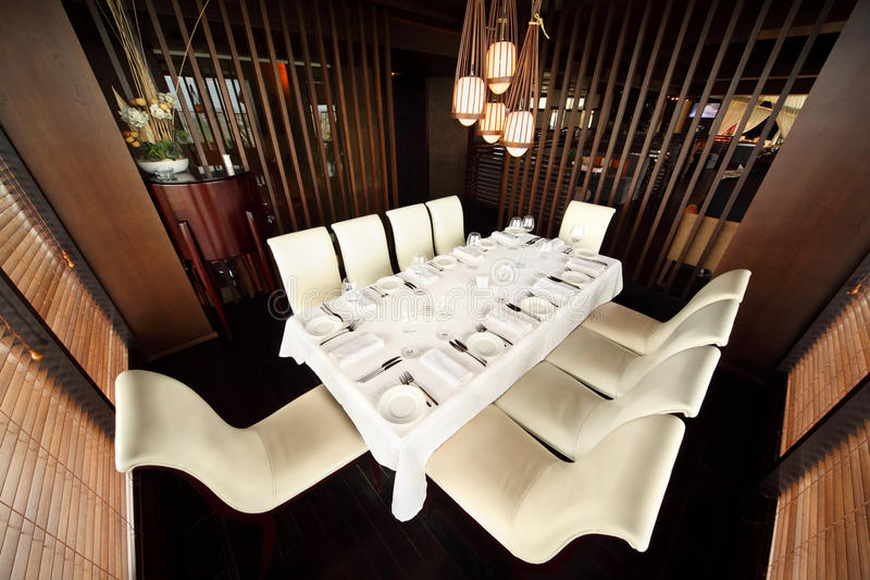 Table and ten white chairs in empty restaurant. Beautiful table with white tablecloth and serving and ten white chairs in empty restaurant royalty free stock photography