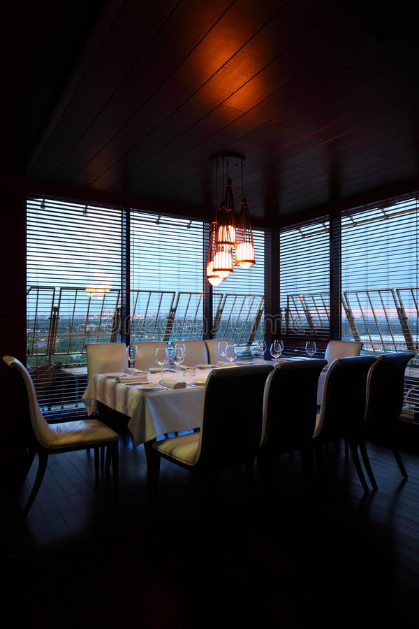 Table and ten white chairs in empty restaurant. Table with white tablecloth and serving and ten white chairs in empty restaurant at evening stock photos