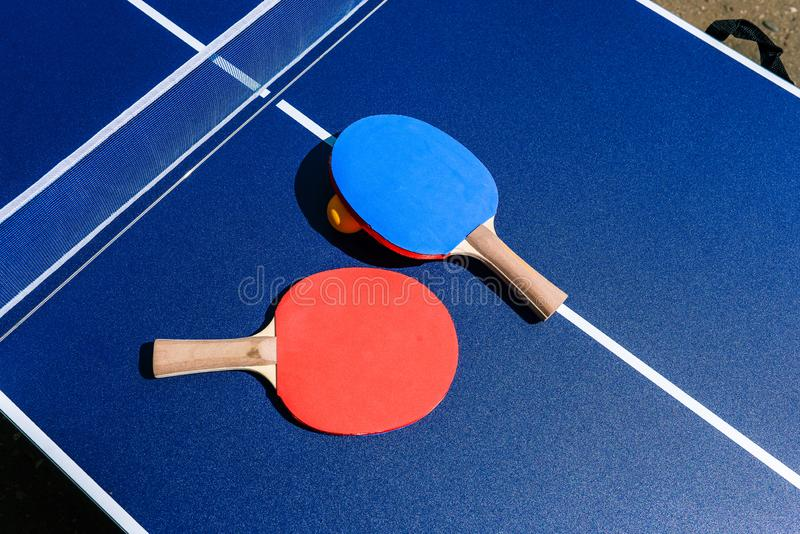 Table tennis equipment - rackets, table and ball. Playing ping pong in the street. Sports ground for outdoor activities. The royalty free stock image