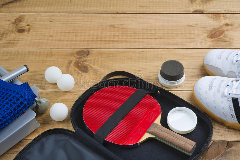 Table tennis paddle in open case with other mandatory equipment. On wooden background stock photo