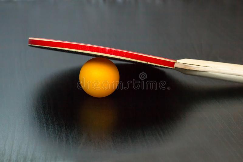 table tennis or ping pong racket and ball on a black background royalty free stock images