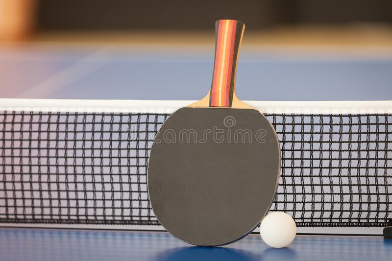 Table tennis or ping pong racket and ball on blue table, net royalty free stock photo
