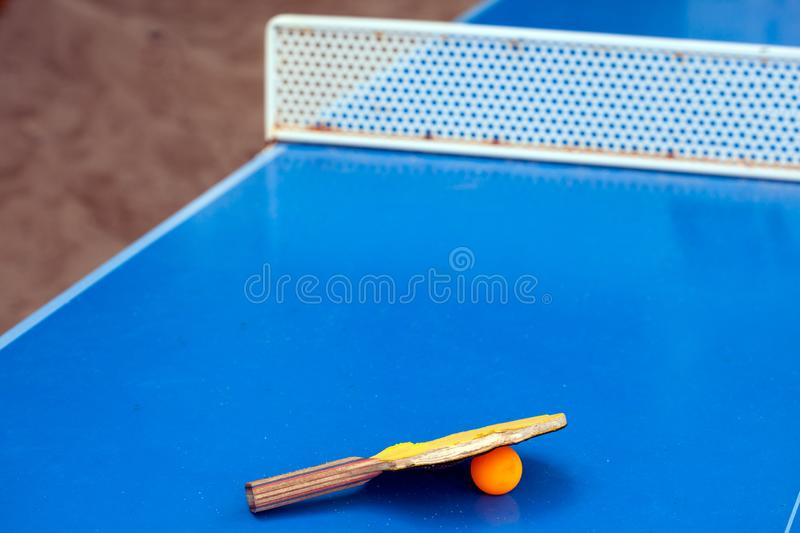 Table tennis or ping pong racket and ball on a blue table stock photography