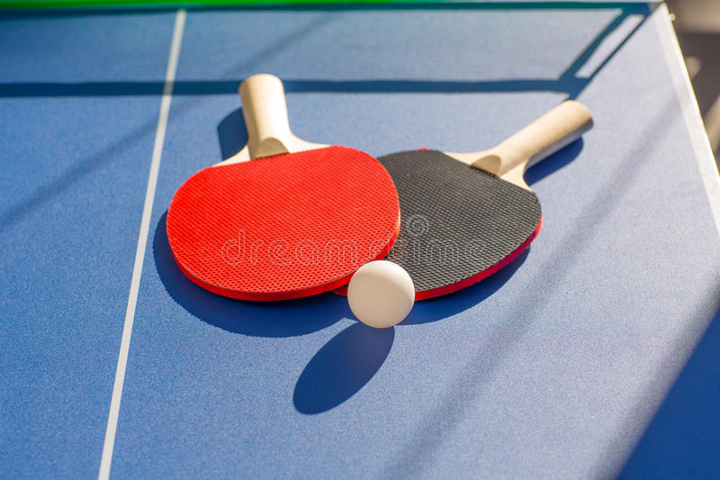 Table tennis ping pong two paddles and white ball. On blue board royalty free stock image
