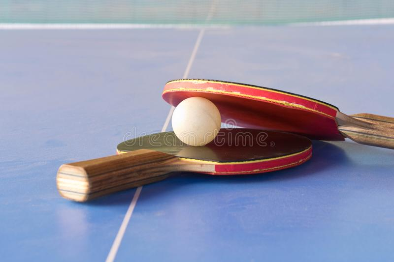 Table tennis rackets and a ball on the table stock photos