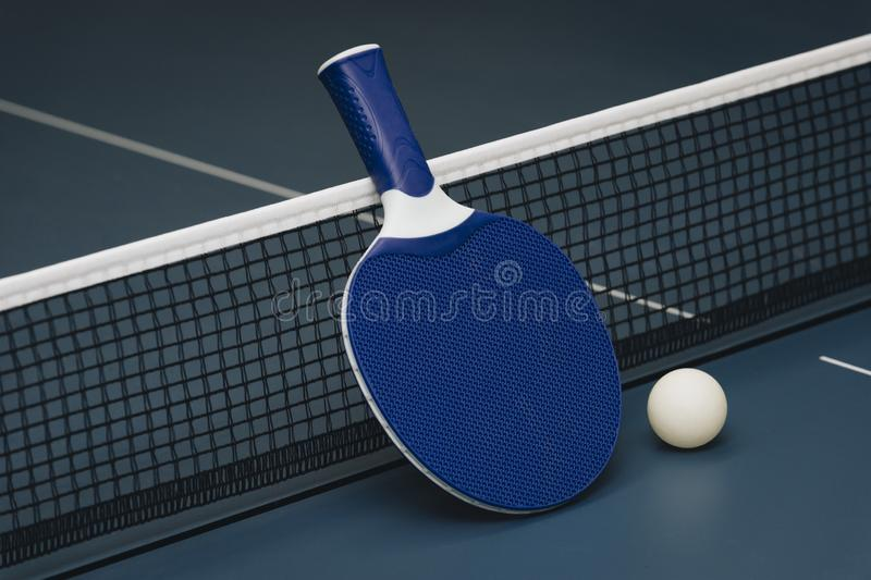 Table tennis rackets and ball and net on a blue pingpong table stock photos