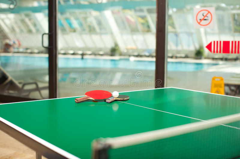 Table tennis rackets and ball swimmig pool stock image