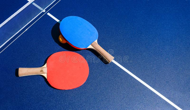 Table tennis. Two rackets of red and blue color lie on a blue table. The concept of a healthy lifestyle and sports. Copy space. stock photo