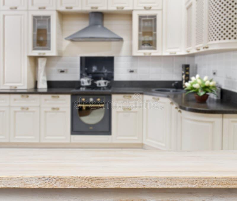 Table texturisée en bois au-dessus de fond brouillé d'intérieur de cuisine image stock