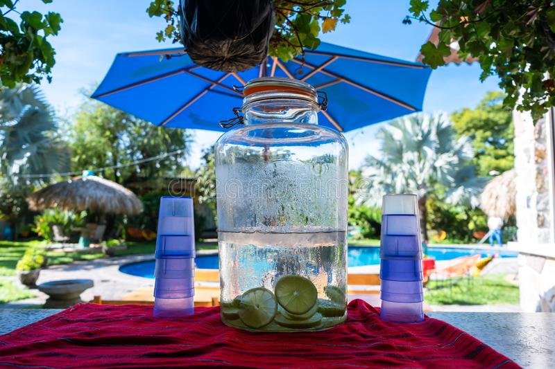 On the table there is a jug with very cold lemon water for people to serve. royalty free stock images