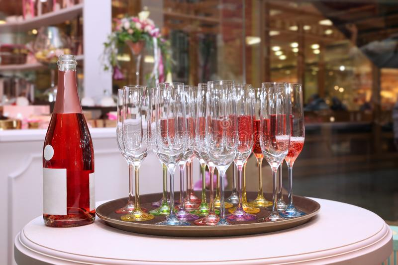 On the table there are many beautiful glasses of champagne and a bottle of wine. On the table there are many beautiful glasses of pink champagne and a bottle of royalty free stock image