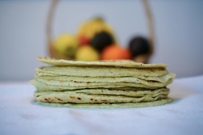 On the table there are tortillas of cactus leaves and a basket of fruits. stock photo