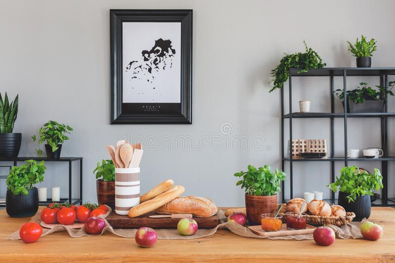 Table with tomatoes, bread, apples and herbs in a rustical dining room interior royalty free stock images
