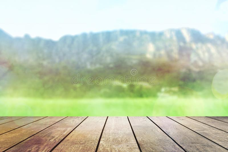 Table top with background mountains, sky and cloud in sunny day for product display job showing. Wooden table on blurred abstract. Table top with background royalty free stock photography