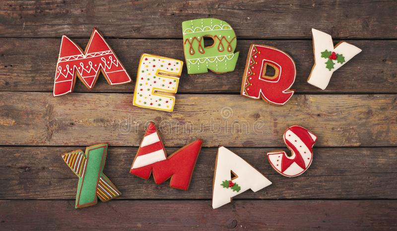 Merry Xmas. Table top shot of nicely decorated gingerbread cookies with white icing shaped like letters Merry Xmas royalty free stock photography