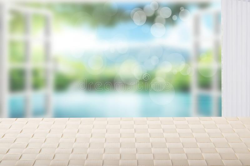 Table top on sunny beach background. A empty bright table on blurred abstract beach with blue sky and bokeh lights. Template for stock photography