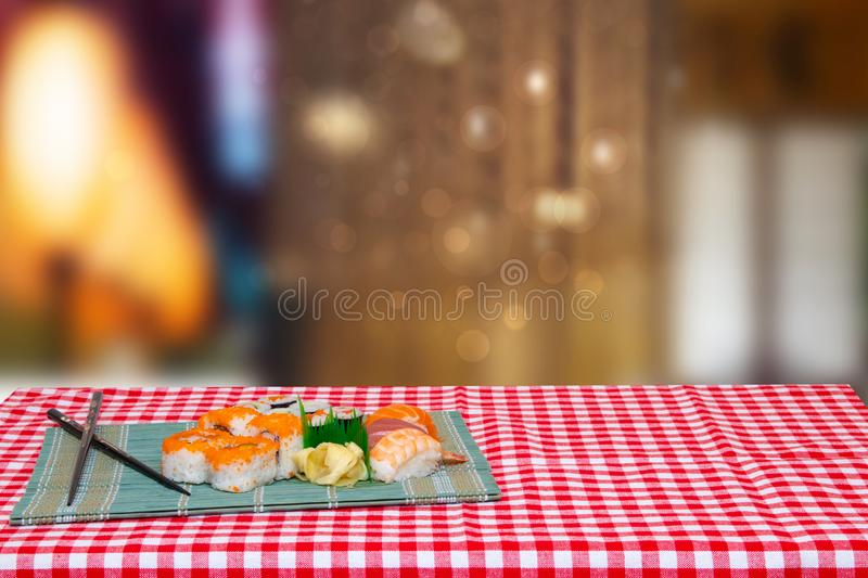 Table top on sushi background. Closeup of various kinds of sushi and chopsticks served on green bamboo mat on a red checkered royalty free stock photo