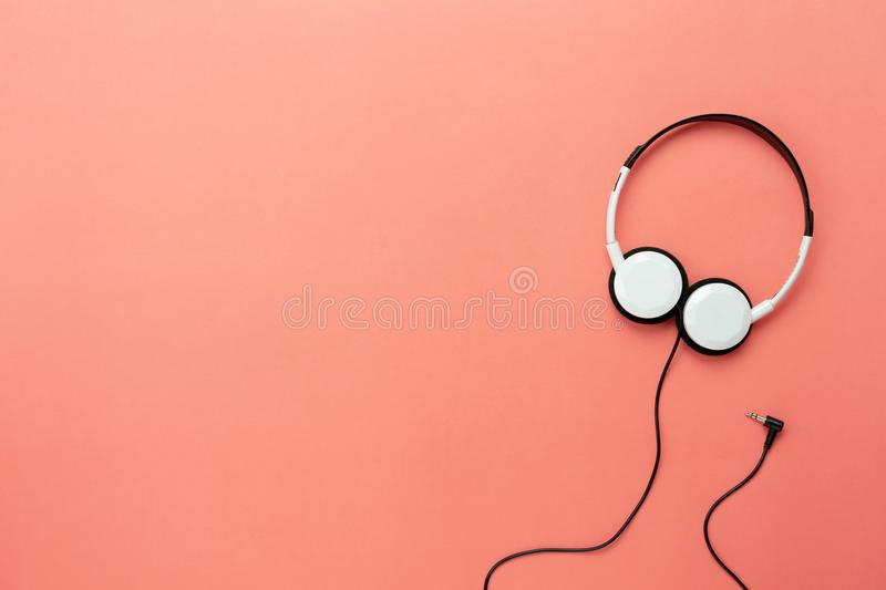 Flat lay white headphones on modern rustic pink paper wallpaper. Table top view aerial image of accessories listening radio music background concept.Flat lay royalty free stock photos