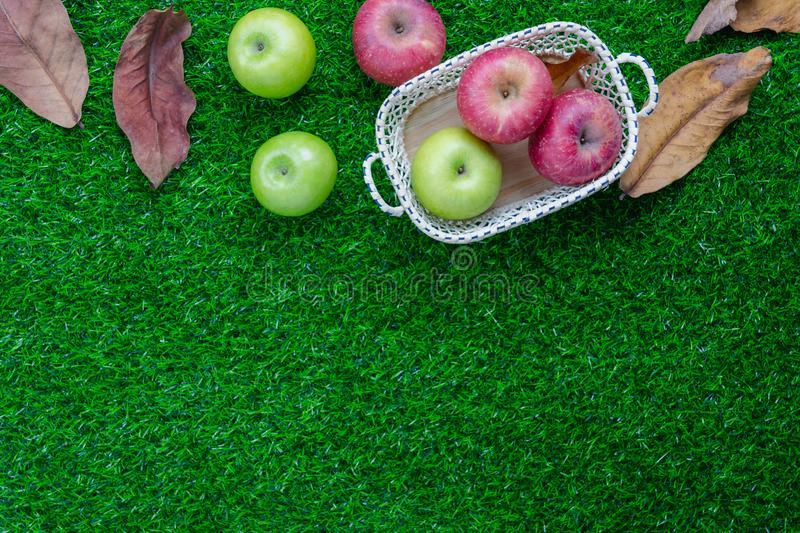 Table top view aerial image of decoration Fall harvest season or Rosh Hashanah day. Background concept.Flat lay green& red apple in wood basket with dry leaf royalty free stock photography
