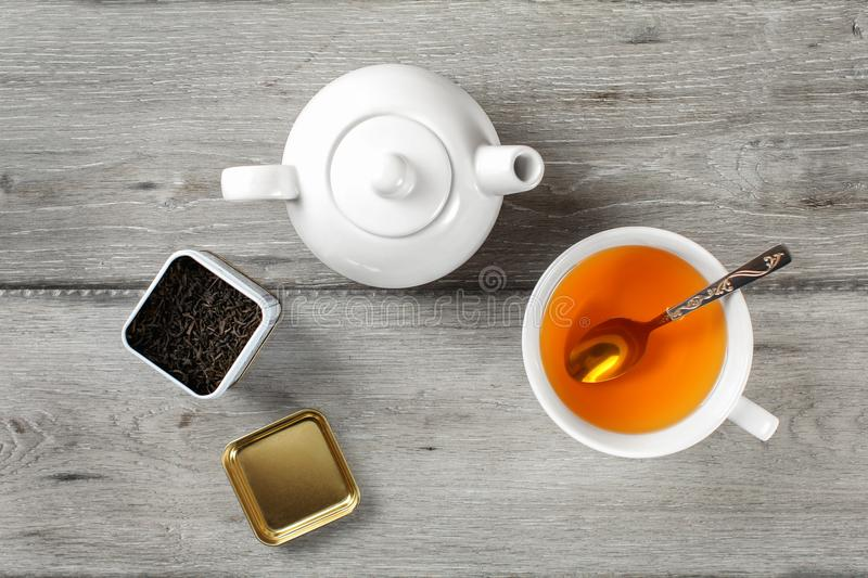 Table top view - brass tea caddy, white porcelain teapot and ceramic cup with silver spoon and hot amber drink, on gray wood desk. stock photo