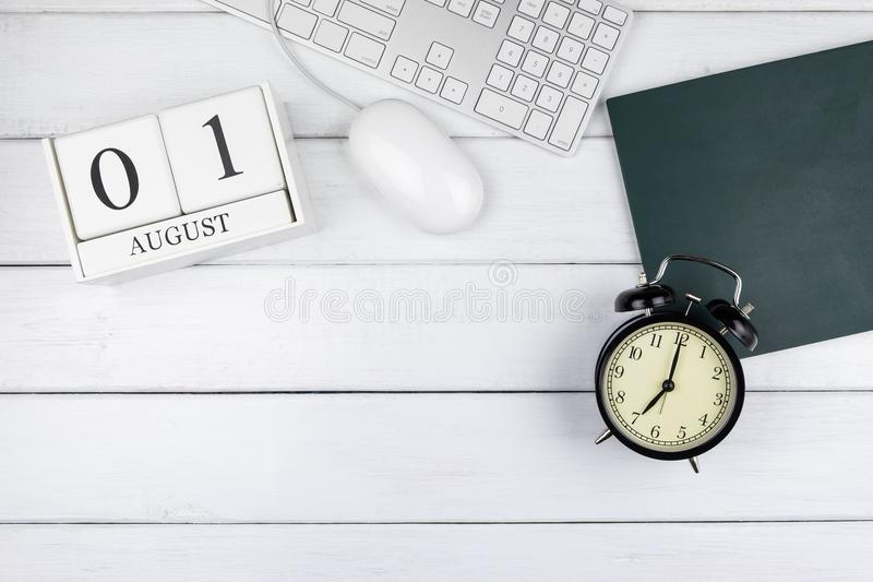 Table top view of calendar, clock, keyboard and mouse. On white wooden office desk stock photography