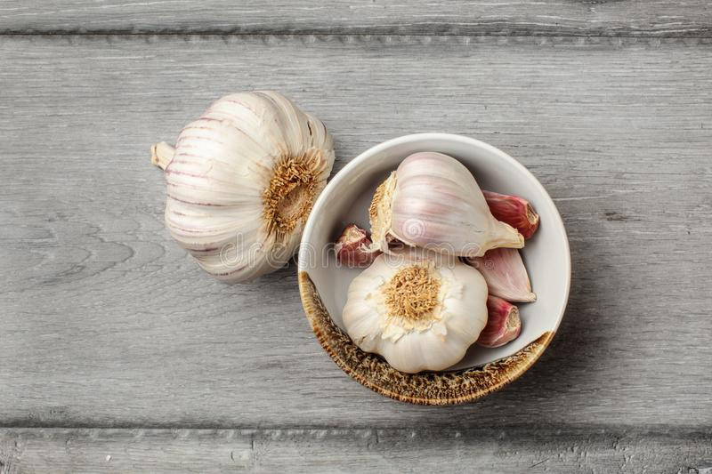 Table top view on garlic bulbs and peeled cloves in small ceramic bowl placed on gray wood desk. stock images