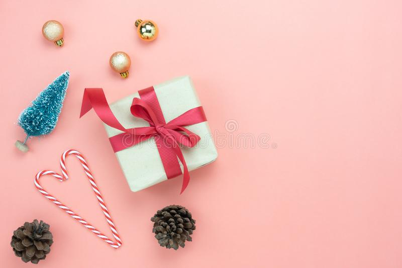 Table top view of Merry Christmas decorations & Happy new year ornaments concept. Flat lay essential difference objects gift box & fir tree on modern pink paper stock photo