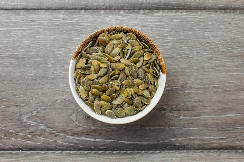 Table top view on small glass bowl full of roasted salted pumpki. N seeds on a gray wood desk stock photography