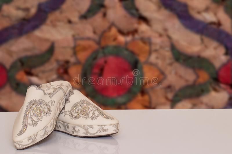 Table top on woman slippers background. Closeup of elegant luxurious handmade beige ladies slippers with beautiful floral. Embroidery and rhinestones over stock photo
