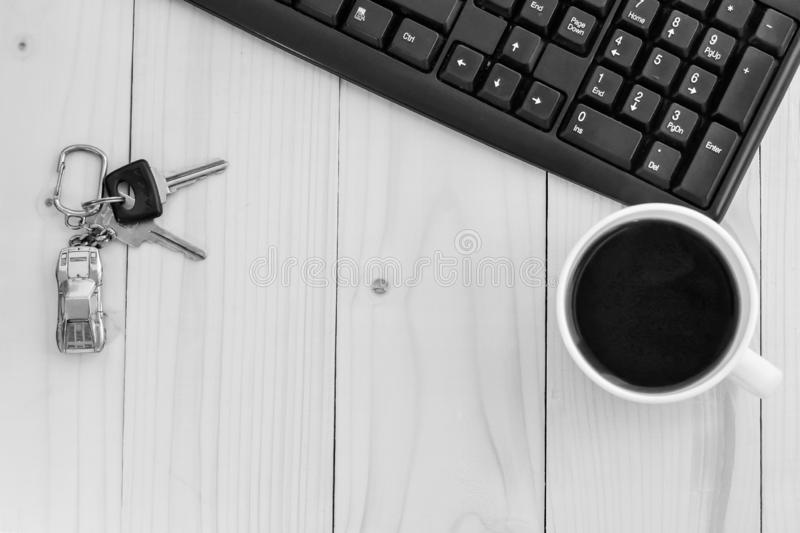 Table top.Computer. Coffee. Key. reyring. On the wooden table are keys to the car with a keychain in the form of a car, The edge of the keyboard is visible royalty free stock photos