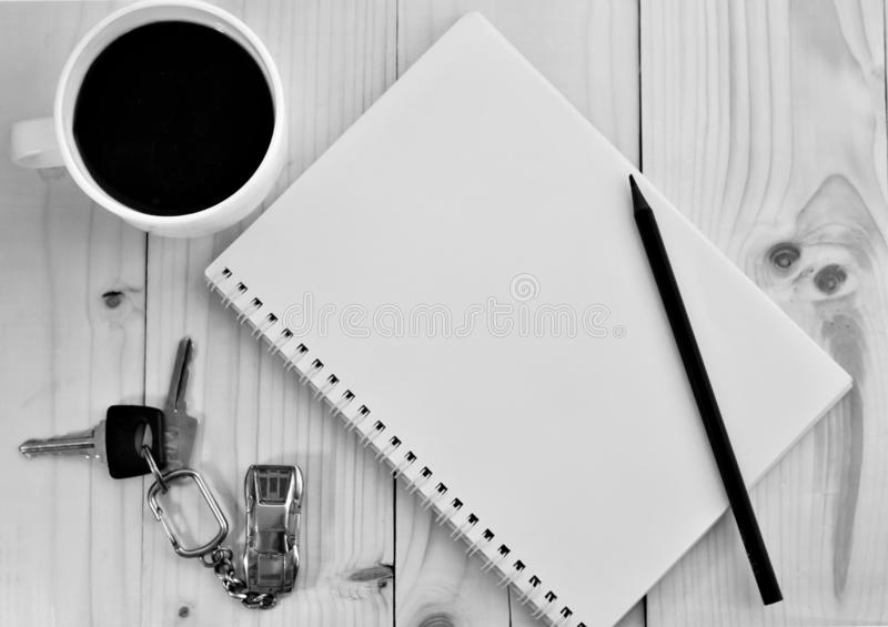 Table top.Computer. Coffee. Key. reyring. On the wooden table are keys to the car with a keychain in the form of a machine, a notebook and a pencil lying on a royalty free stock images