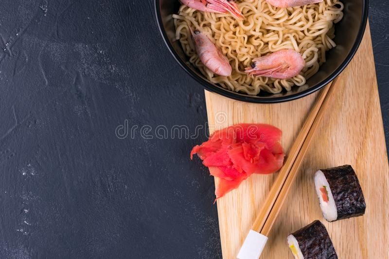 Table with traditional Japanese cuisine noodles and sushi rolls.  stock image