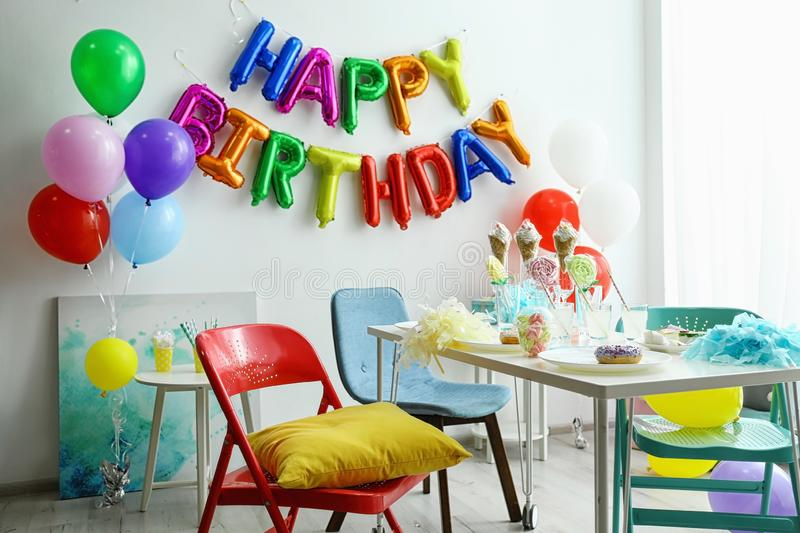 Table with treats and phrase HAPPY BIRTHDAY made of colorful balloon letters stock images