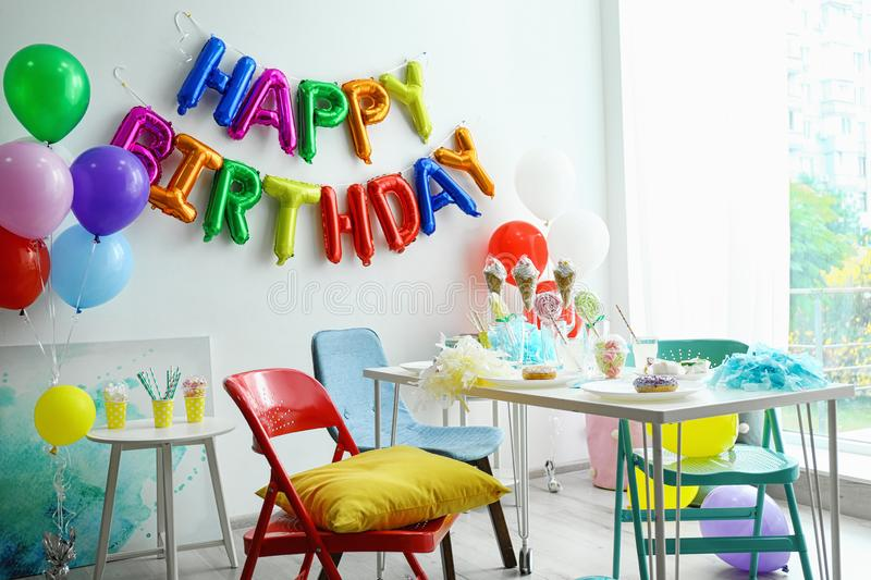 Table with treats and phrase HAPPY BIRTHDAY made of colorful balloon letters royalty free stock photography