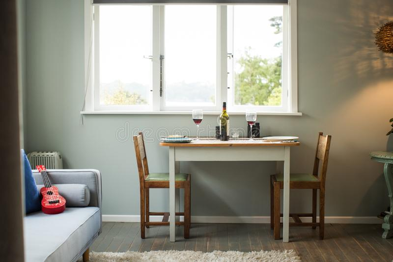 Table for two people near the window with wine glasses and a wine bottle on it royalty free stock photos