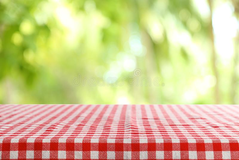 Table vide avec la serviette rouge à carreaux sur le fond brouillé vert photos stock