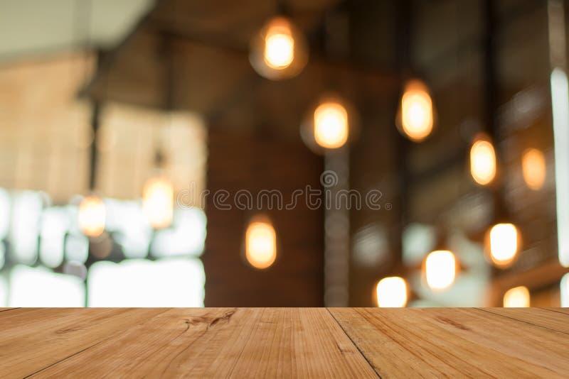 Table vide de conseil en bois devant la lampe brouillée de café images libres de droits