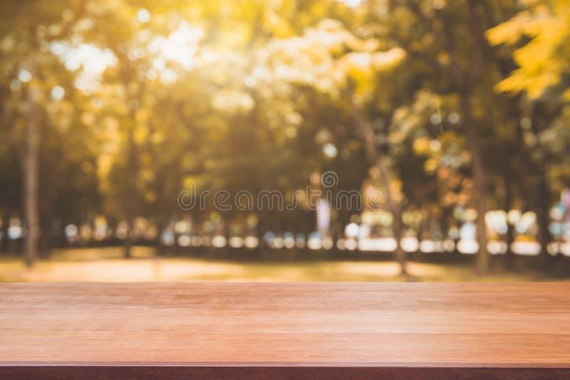 Table vide de conseil en bois devant le fond brouillé Table en bois brune de perspective au-dessus des arbres de tache floue à l' photos stock