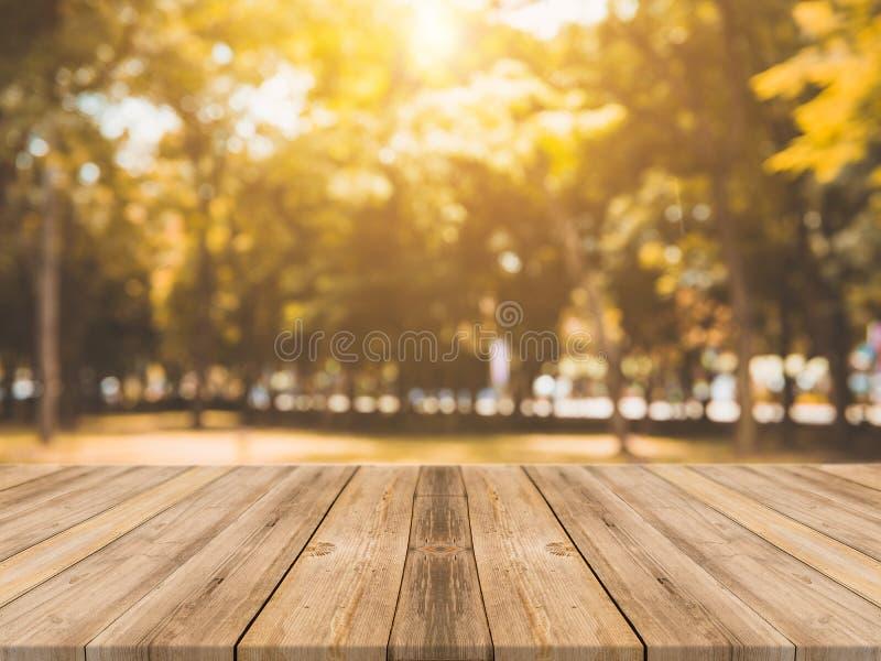 Table vide de conseil en bois devant le fond brouillé Table en bois brune de perspective au-dessus des arbres de tache floue à l' image libre de droits