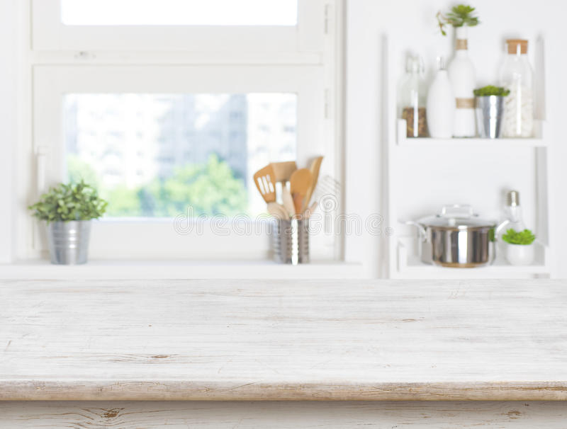 Table vide sur le fond brouillé de la fenêtre et des étagères de cuisine images libres de droits