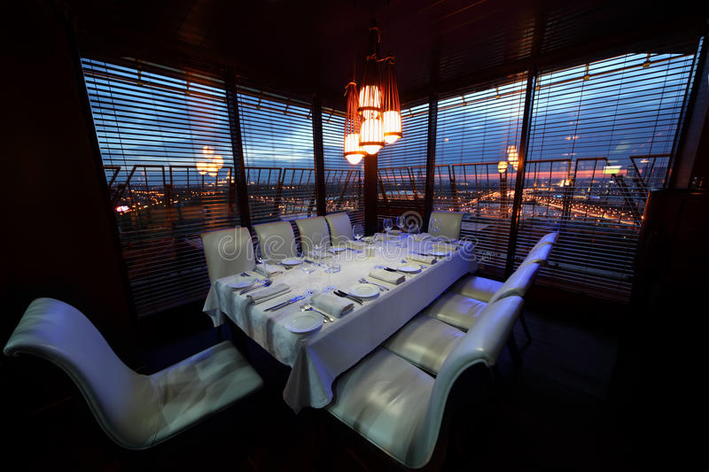 Table and white chairs in restaurant. Table with white tablecloth and serving and white chairs in restaurant at night stock images