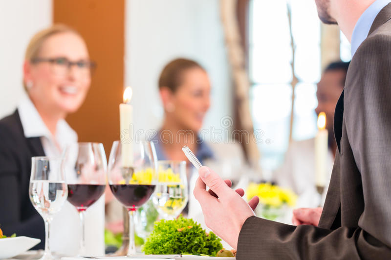 Table with wine at business lunch in restaurant. Team having business lunch in restaurant toasting with red wine to celebrate royalty free stock image