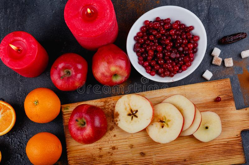 On the table, slices of apples, whole apples and an orange, a plate with cranberries and candles. View from above. stock photography