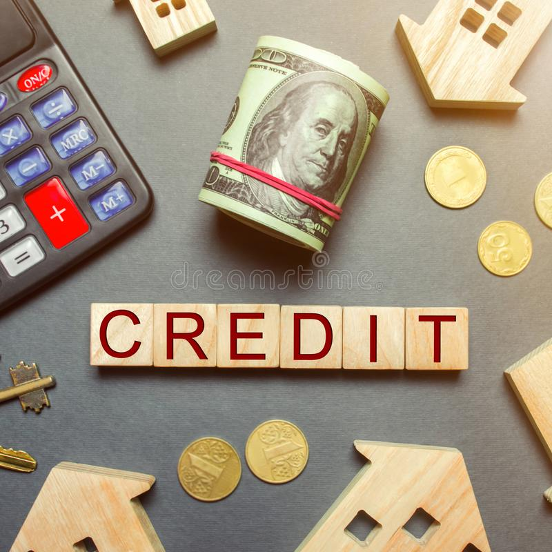 Table with wooden houses, calculator, coins, magnifying glass with the word Credit on wooden blocks. Buying a home in debt. Credit stock photos